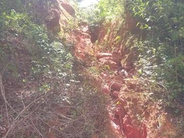 Lamaçal com pedras rola de morro para a margem da BR 262